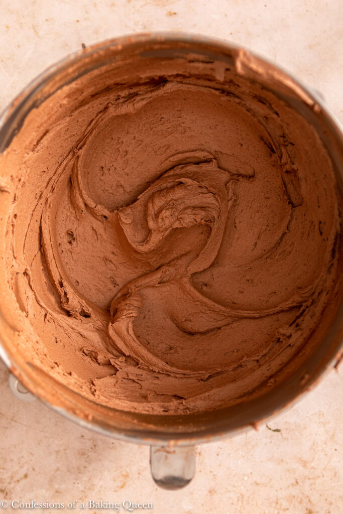 close up of chocolate buttercream in mixing bowl on a light brown surface