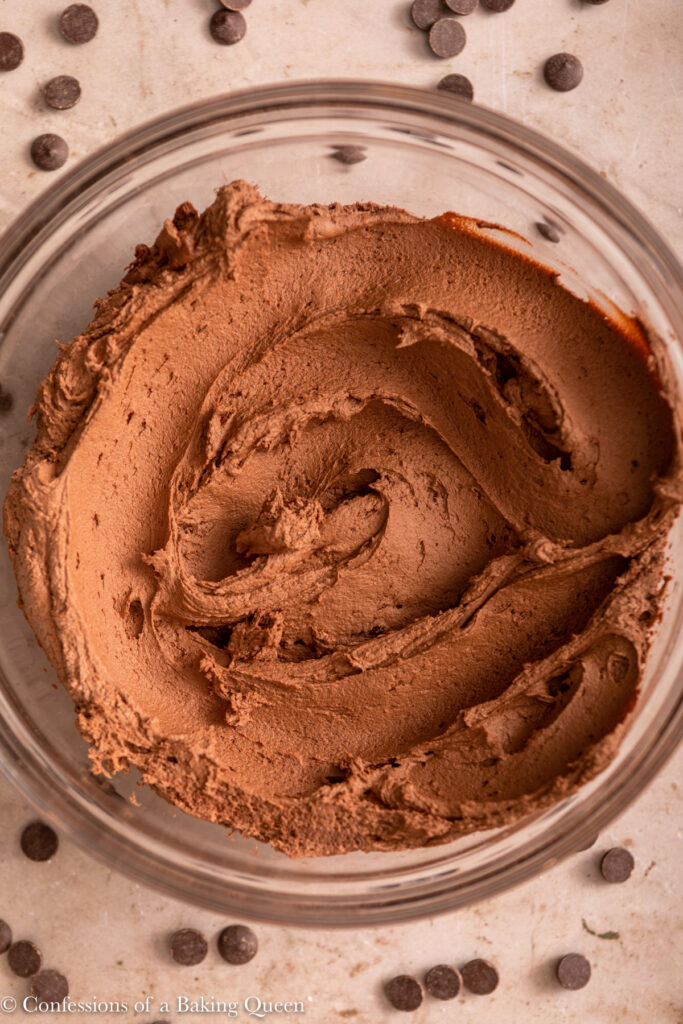 close up of chocolate frosting in a glass bowl next to chocolate chips on a light brown surface