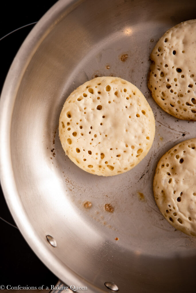 close up of crumpets cooking in a metal pan