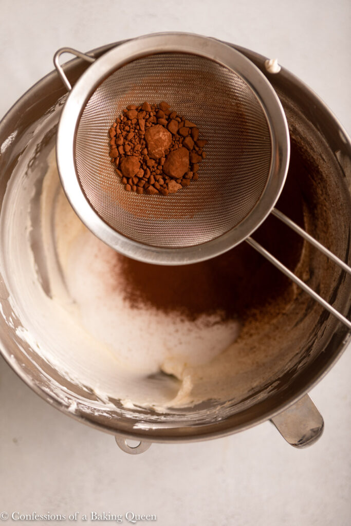 cocoa powder sifted into cheesecake batter in a metal mixing bowl on a light grey surface