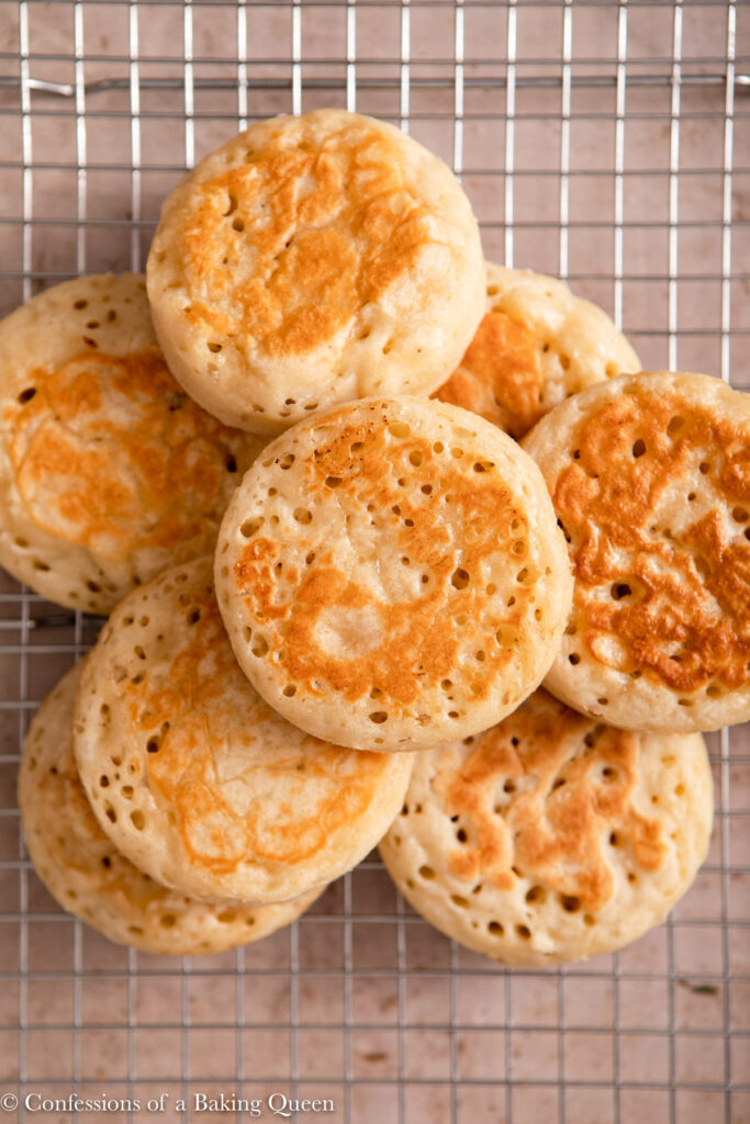 crumpets stacked on top of each other on a wire rack on a light brown surface