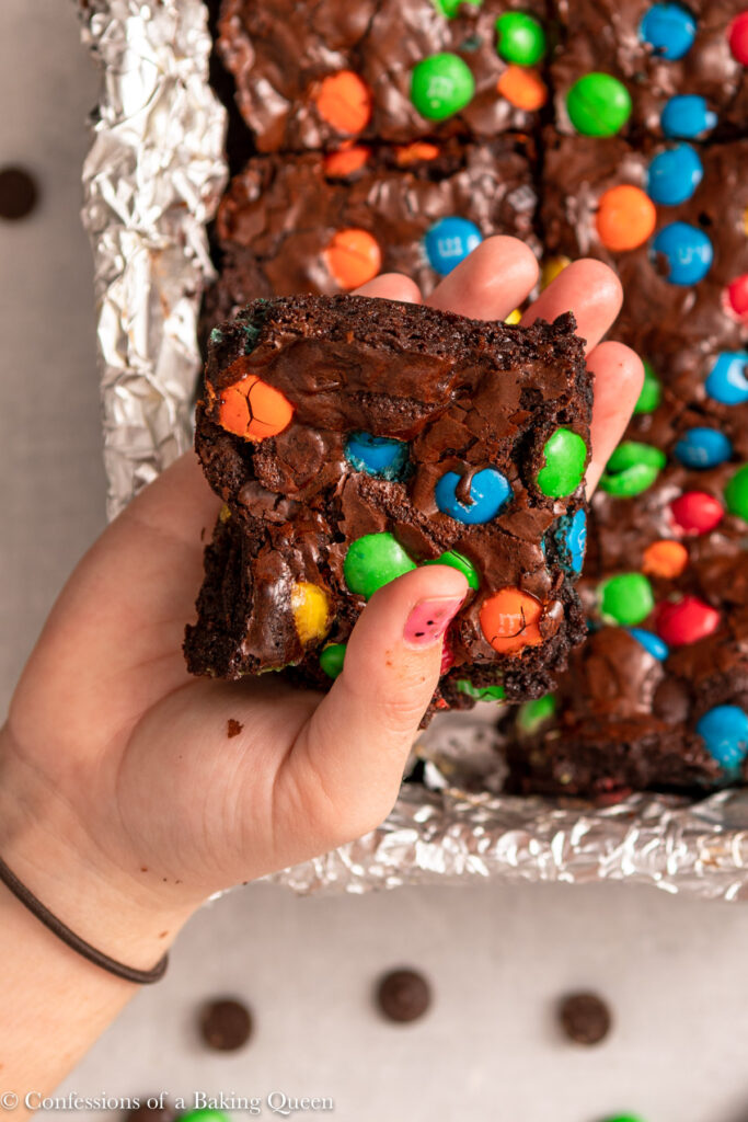 hand holding a piece of m&m brownie over a tray of brownies