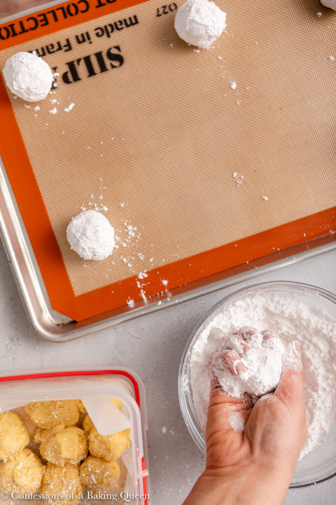 hand holding orange crinkle cookie dough ball in a bowl of powdered sugar next to a cookie sheet and container of cookie dough
