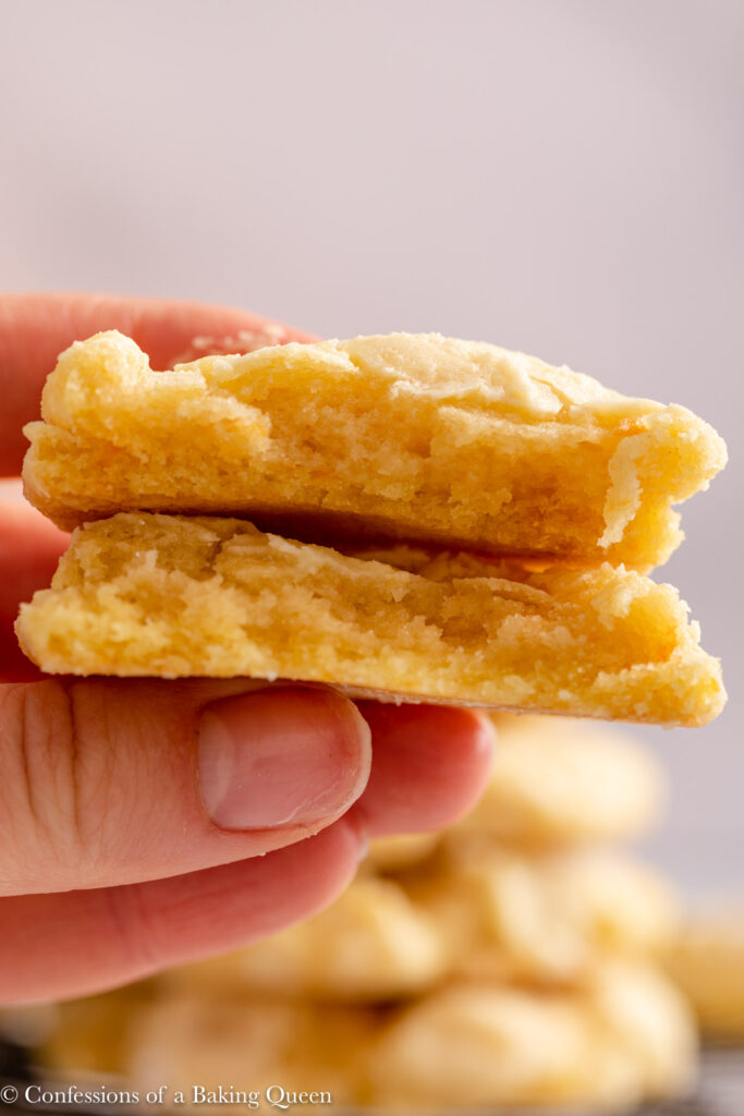 hand holding two pieces of orange crinkle cookies in front of a stack of cookies