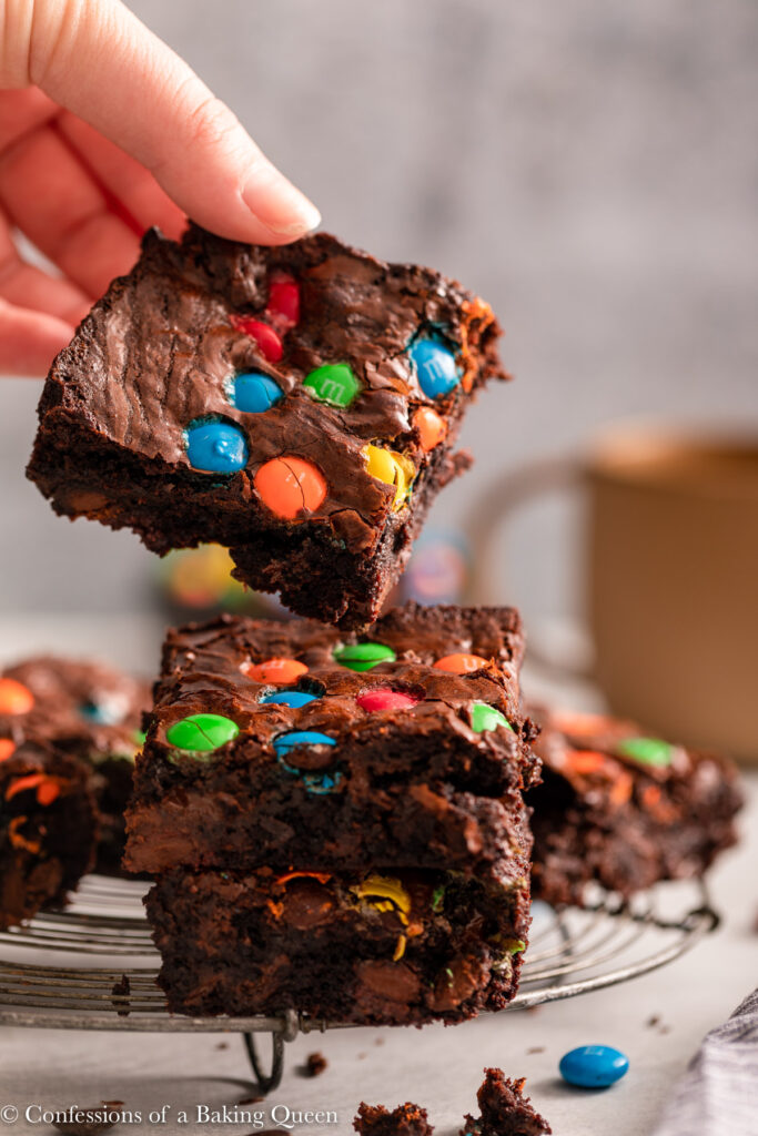 hand taking an m&m brownie from a stack on a wire rack on a light grey surface
