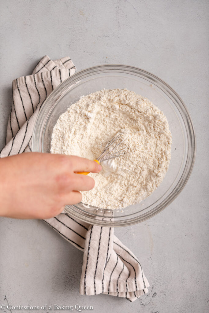hand whisking dry ingredients together in a glass bowl on a light grey surface with a white and blue linen