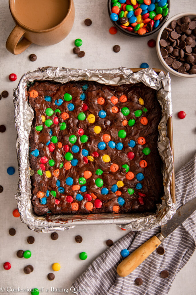 m and m brownies after baking on a light grey surface next to a cup of coffee and bowl of m&ms and chocolate chips