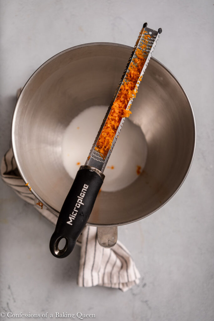 micropane zester with lots of orange zest over a bowl of sugar on a light grey surface