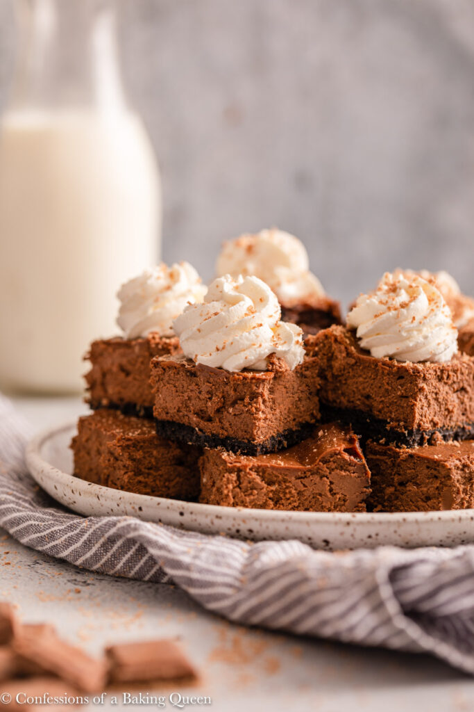 mini chocolate cheesecake bars stacked on a plate on top of a blue and white linen with a milk bottle in the background