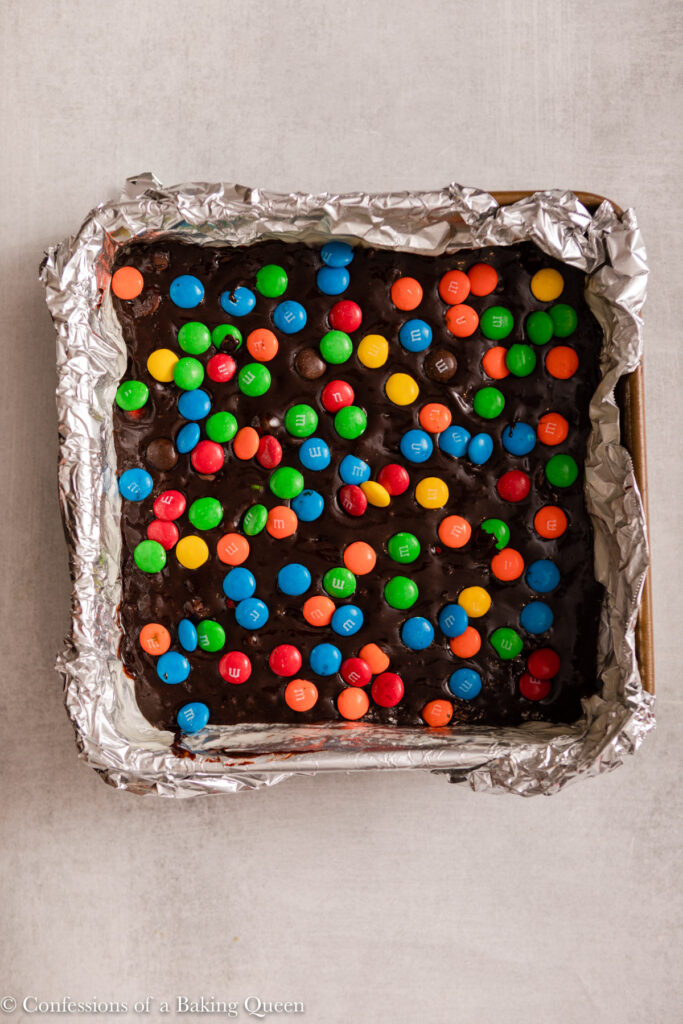 m&ms added on top of brownie batter before baking on a light grey surface
