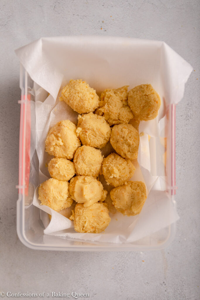 orange crinkle cookie dough balls on parchment paper in a plastic container on a light grey surface