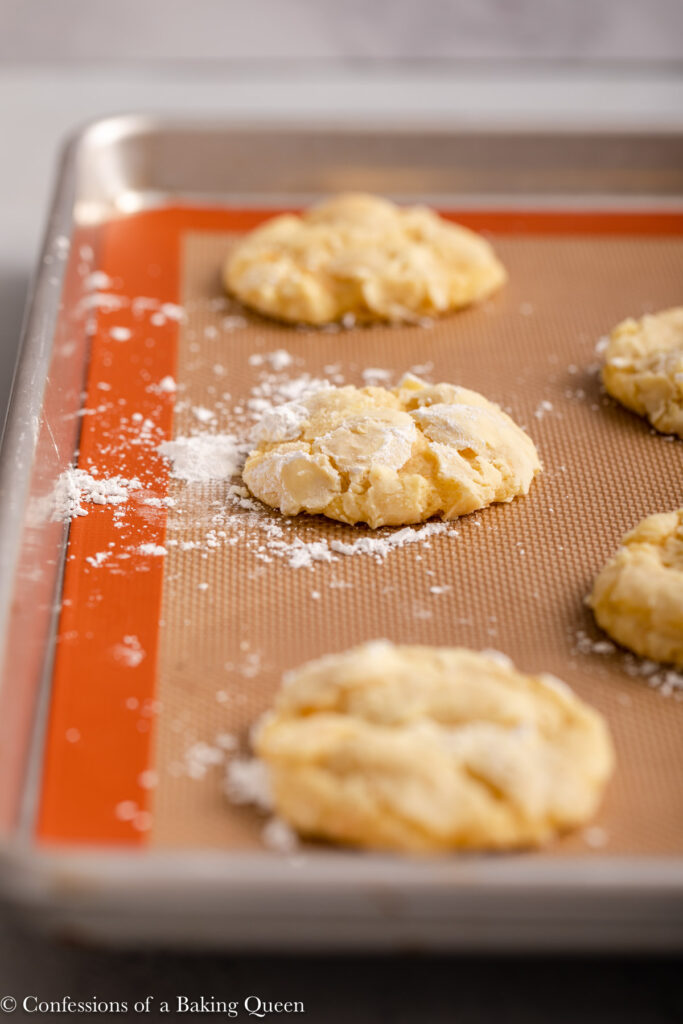orange crinkle cookies after baking on a silpat lined baking sheet on a light grey surface