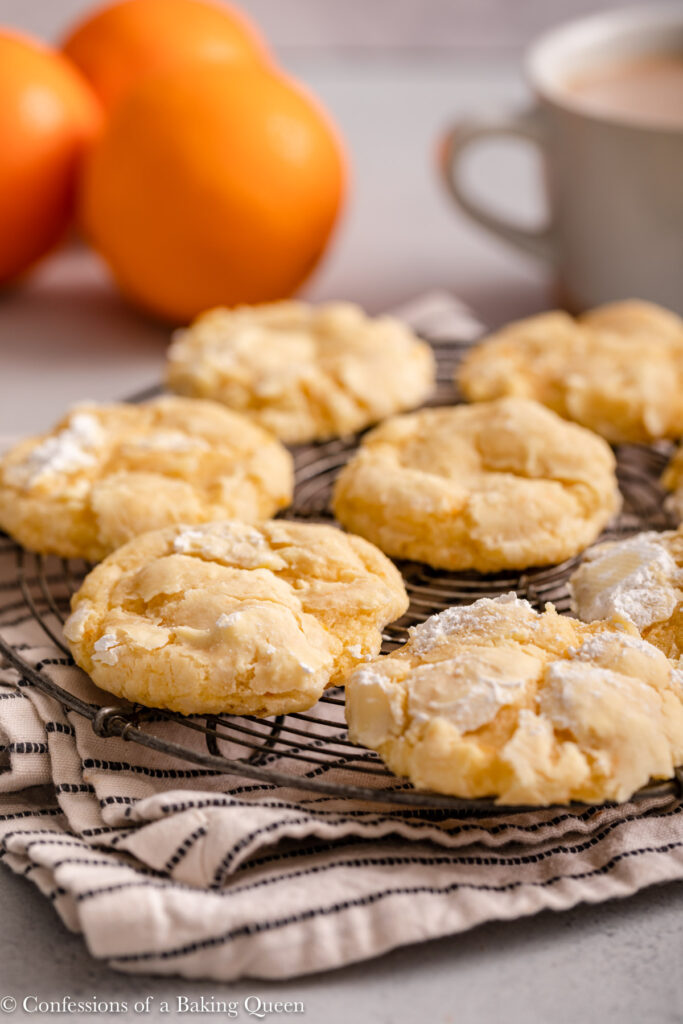 orange crinkle cookies on a wire rack on top of a linen with oranges in the background