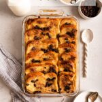 bread and butter pudding, glass of milk, plates and spoons on a light grey background