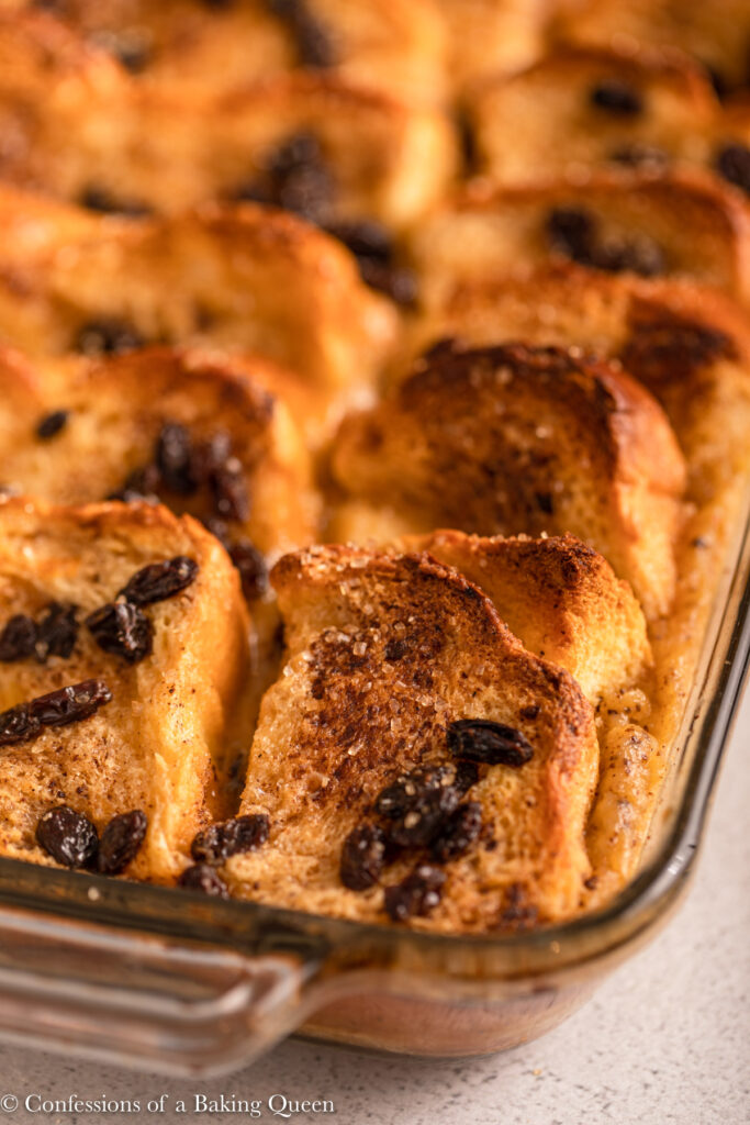 close up of bread and butter pudding in a glass pan on a light grey background