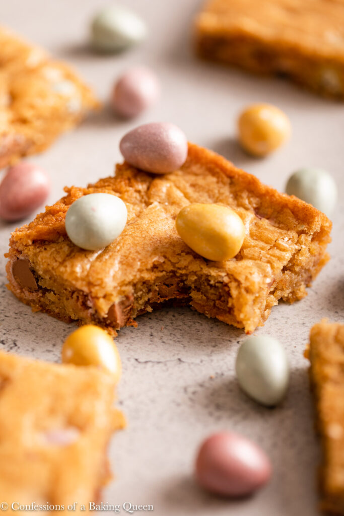 close up of mini egg blondie half eaten next to more blondies and mini eggs on a light grey surface