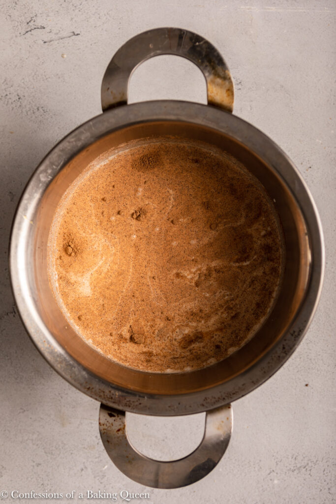 liquid ingredients for custard in metal pot on a light grey background