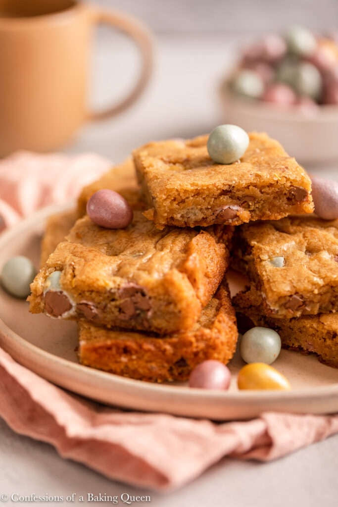 plate full of mini egg blondies on top of a light pink surface with a cup of coffee and bowl of mini eggs on alight grey surface