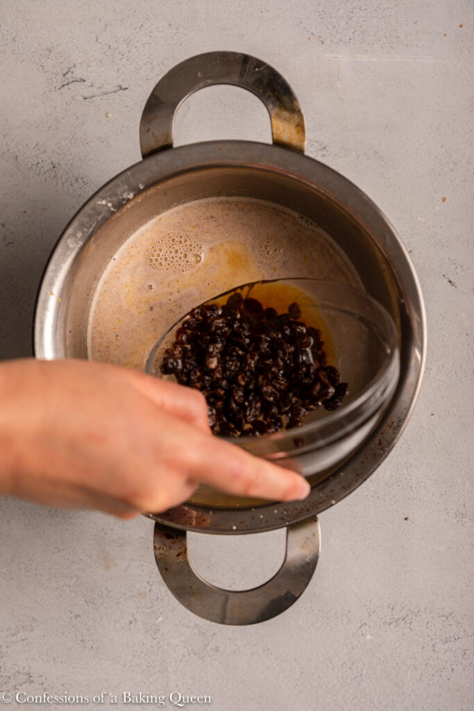 raisins and brandy poured into custard mixture in a metal pot on a light grey background
