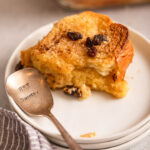 slice of bread and butter pudding on a white plate on top of a blue and white linen on a light grey background