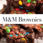 close up of m&m brownie on top of more brownies on a light pink plate on top of a blue linen on a grey surface