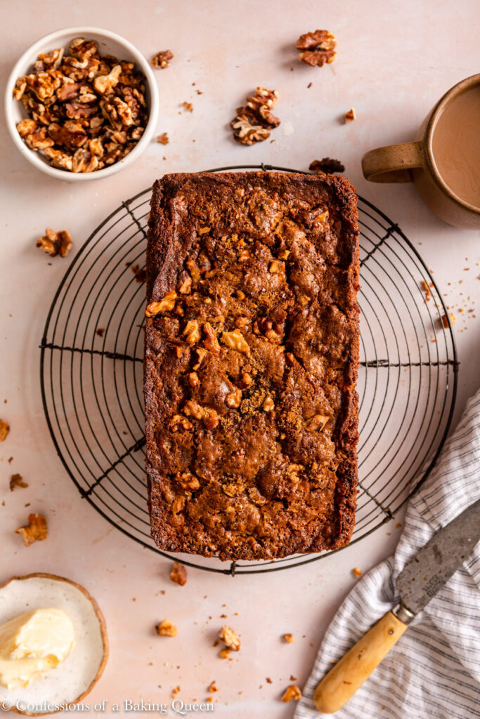 banana walnut bread cooling on a wire rack next to a cup of coffee, bowl of walnuts, butter plate, and linen with a knife on a light pink surface