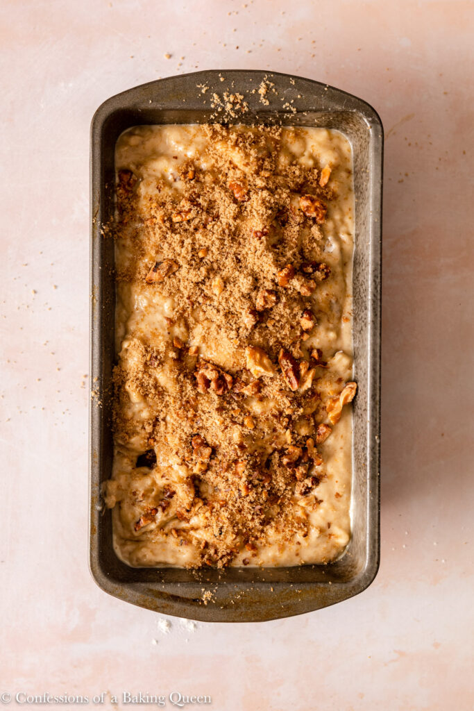 brown sugar sprinkled on top of banana walnut bread before baking in a metal loaf pan on a light pink surface