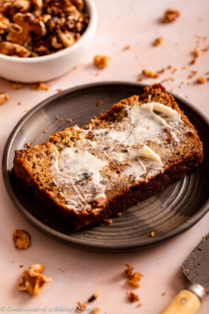 buttered slice of banana bread on a black plate next to a bowl of walnuts and a knife on a light pink surface