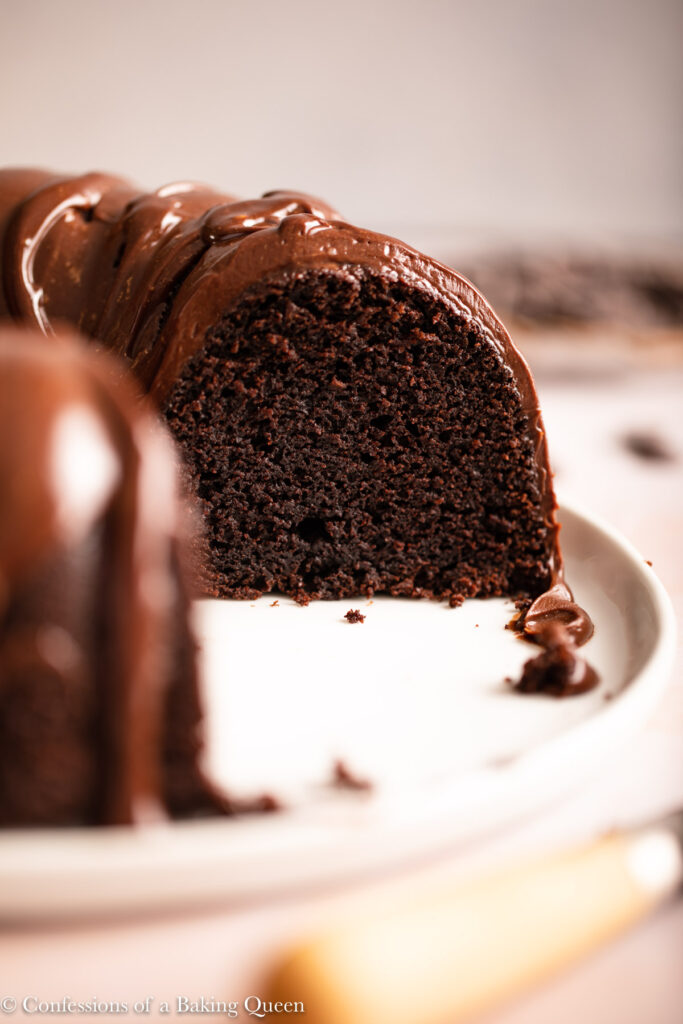 chocolate bundt cake slice on a stack of white plate next to a wooden knife on a light pink surface