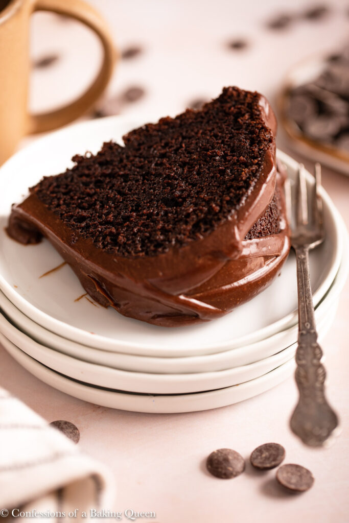 chocolate bundt cake slice on a stack of white plates next to a cup of coffee on a light pink surface