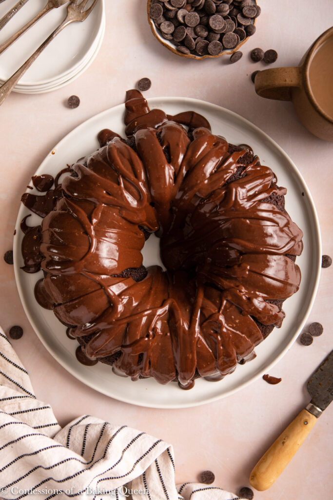 chocolate ganache frosted chocolate bundt cake served on a white plate next to a cup of coffee, knife, plates and forks