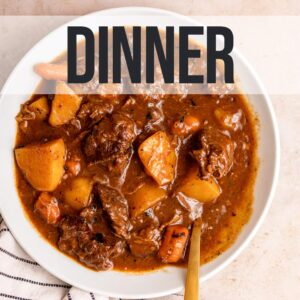 bowl of beef stew with a gold spoon on a light brown spoon