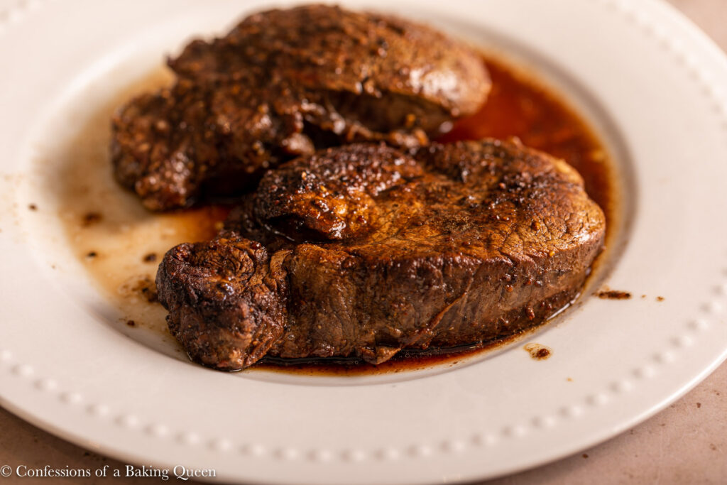 filet mignon after resting on a white plate on a light brown background