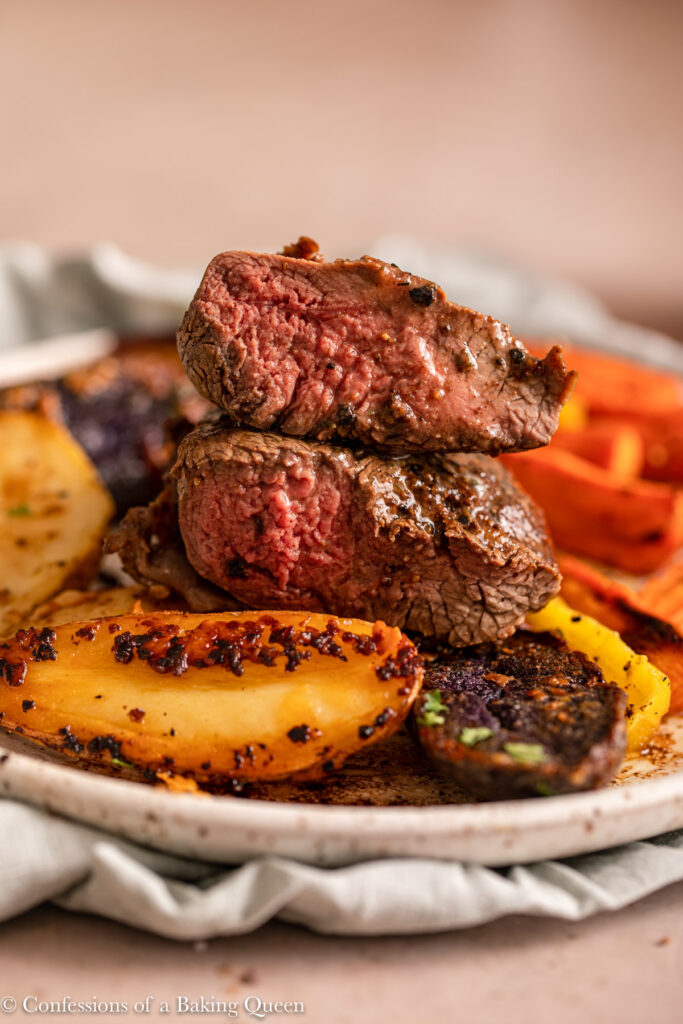filet mignon and roasted fingerling potatoes on a speckled plate on a light brown surface