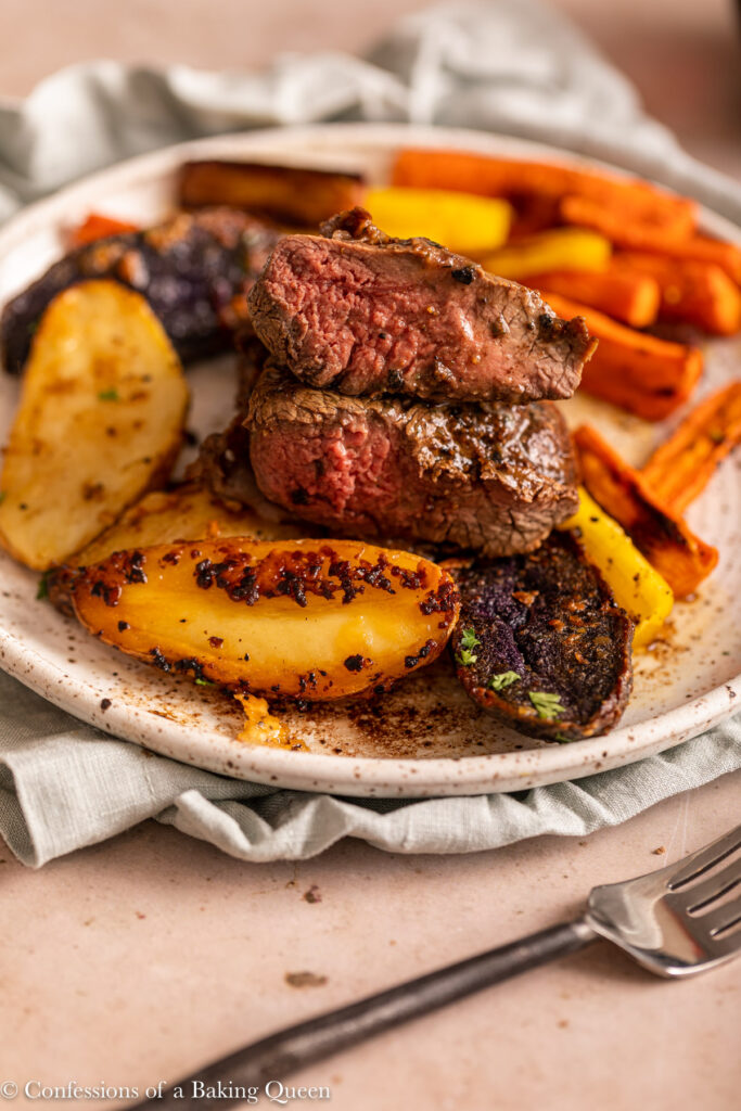 filet mignon sliced in half on top of fingerling potatoes with carrots on a plate on a green linen with a fork on a light brown background