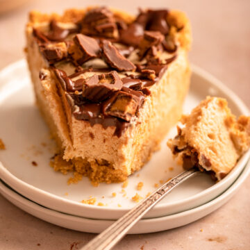 fork taking a bite of chocolate peanut butter pie on a stack of white plates on a light brown surface
