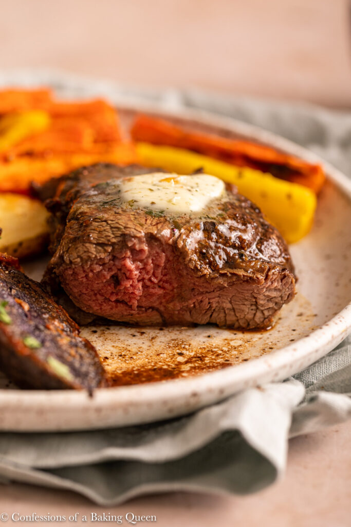 half eaten filet mignon with potatose and carrots on top of a green linen on a light brown background