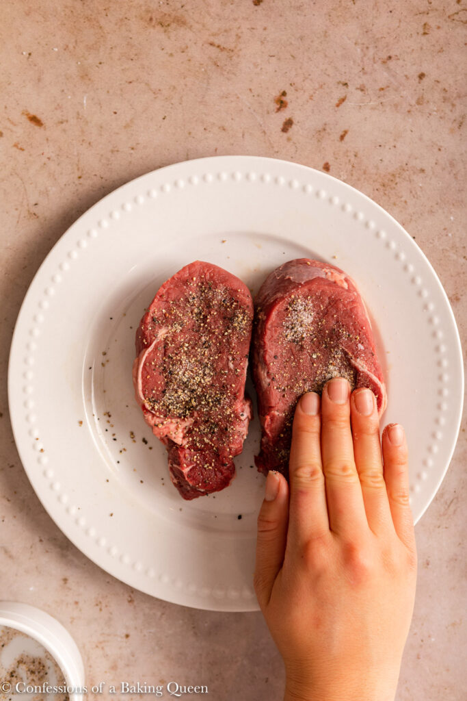 hand pressing salt and pepper into steak on a light brown background