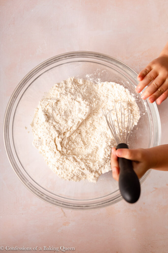 hand whisking dry ingredients together in a glass bowl on a light pink surface