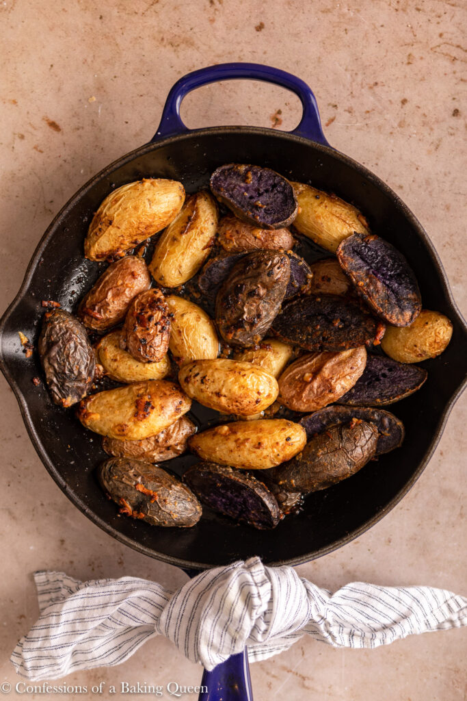 just out of the oven baked fingerling potatoes in a skillet on a light brown surface