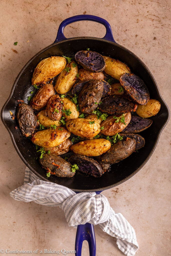 roasted fingerling potatoes in a cast iron skillet with a white and blue linen on a light brown surface