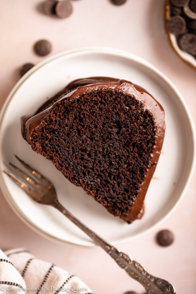 slice of chocolate cake on a stack of white plates  next to another slice of cake and a white stripped linen on a light pink surface