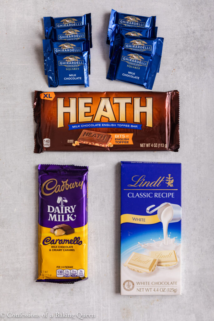 4 different type of chocolate bars on a light grey surface