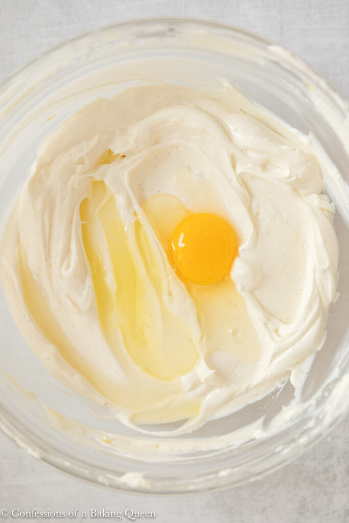 egg added to cheesecake batter in a glass bowl on a light grey surface