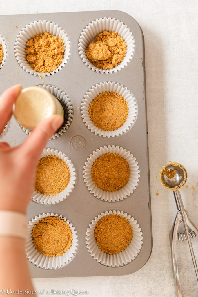 graham cracker crust pressed into cupcake liners with the bottom of a spice jar on a light grey surface