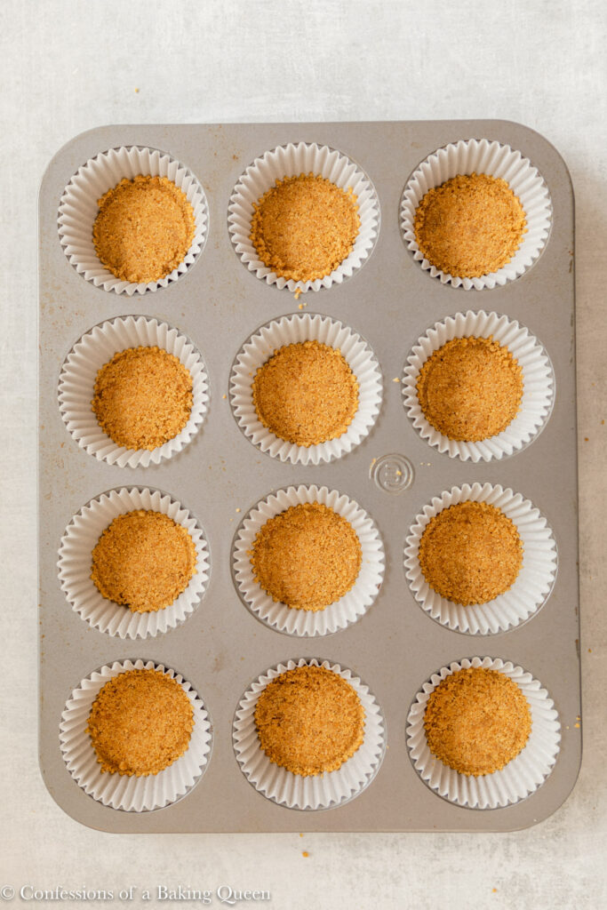 graham cracker crust tightly packed into cupcake liners in a metal pan on a light grey surface