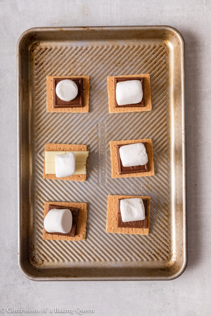 graham crackers with chocolate and marshmallows on a metal sheet pan on a light grey surface