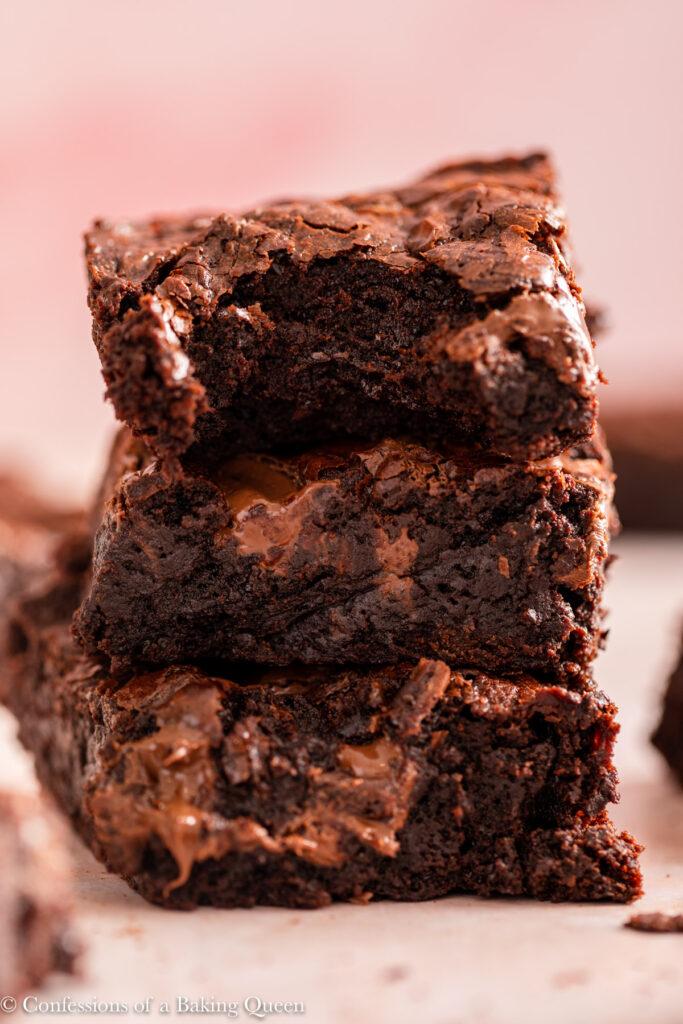half eaten brownie on top of more brownies on a light pink surface on a light pink surface