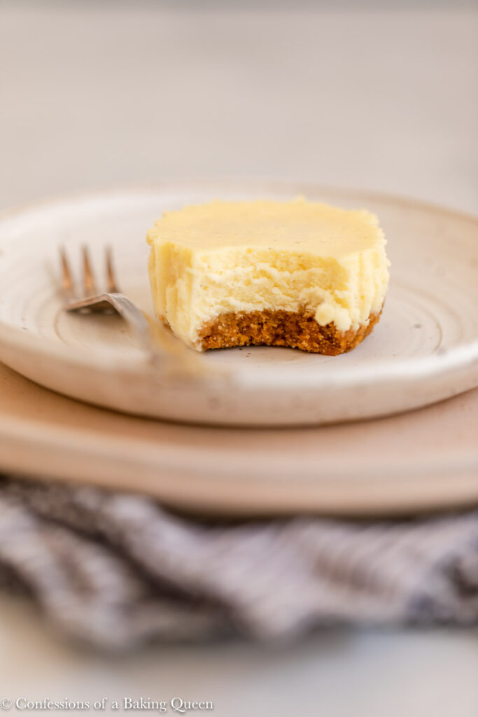 half eaten cupcake cheesecake on a white plate with a fork on a light grey surface