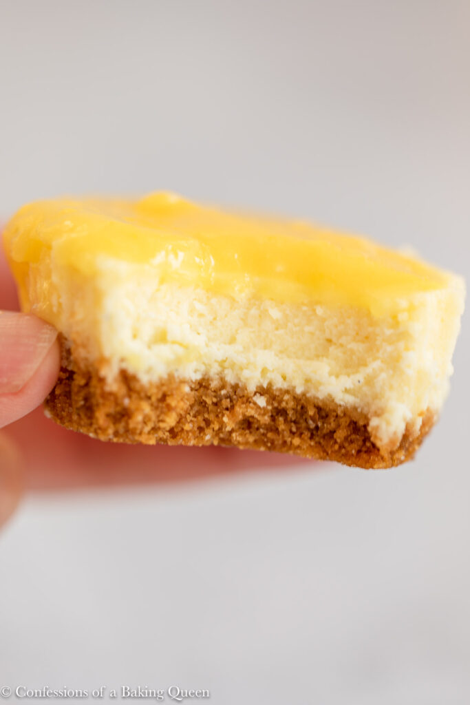 hand holding a half eaten mini lemon curd cheesecake on a light grey surface